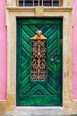 Old wooden door with vintage metal frame pattern