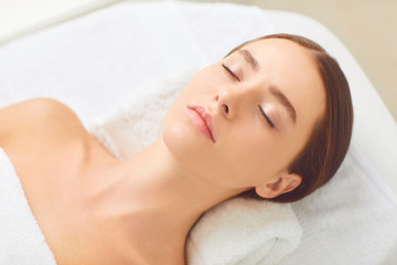 Beauty and spa concept. Brunette girl lying on a massage desk