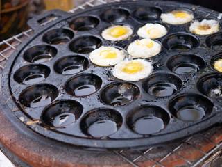 small quail's eggs fry in multi hole flat pan thai style