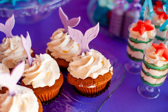 Birthday party concept for girl. Table for kids with cupcakes with withe topind decored purple mermaid tail. Summer season delicious on the party. Sea time theme on the candy bar