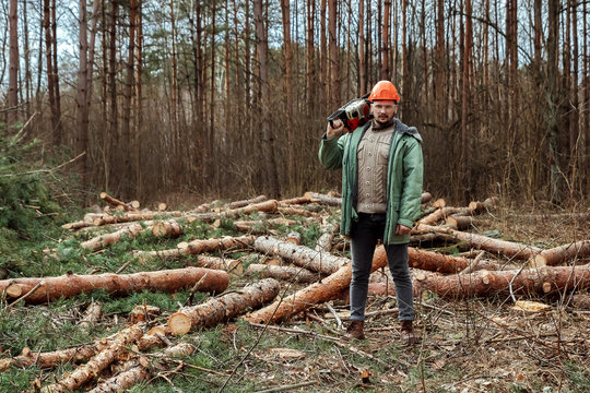 Logging, Worker in a protective suit with a chainsaw. Cutting down trees, forest destruction. The concept of industrial destruction of trees, causing harm to the environment.