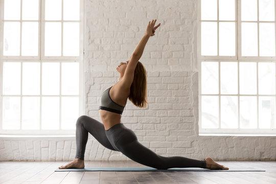 Sporty woman practicing yoga, standing in anjaneyasana pose, Horse rider
