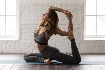 Young woman practicing yoga, Mermaid pose, Eka Pada Rajakapotasana