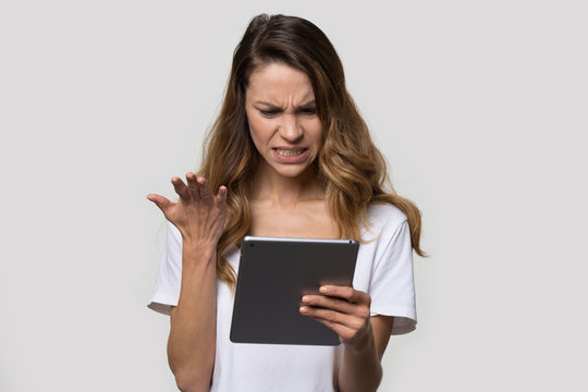 Irritated woman looking at tablet screen feels angry