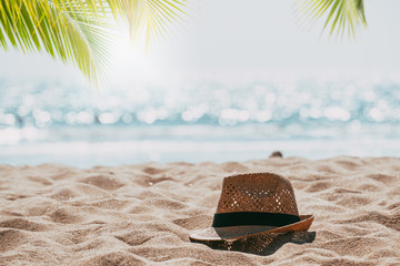 Fotomurales - Straw hat on sand tropical beach seascape with palm tree and blur bokeh light of calm sea and sky background. summer vacation background concept.