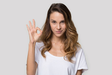 Attractive woman posing in studio showing ok sign