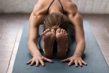 Young woman practicing yoga, Seated forward bend pose, paschimottanasana