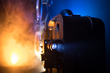 Old vintage movie projector on a dark background with fog and light. Concept of film-making.
