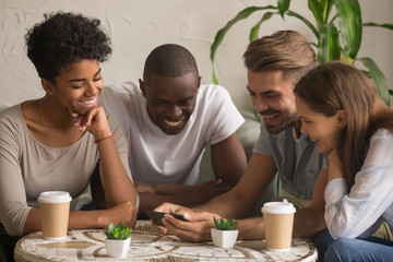 Multi-ethnic happy friends laughing watching funny mobile video on smartphone