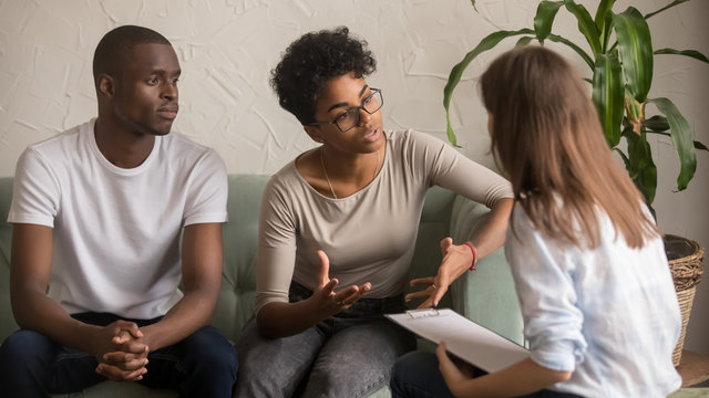 Unhappy african wife talking to psychologist complaining on bad relationship