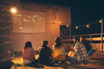 Friends watching a movie on a building rooftop terrace Wall mural
