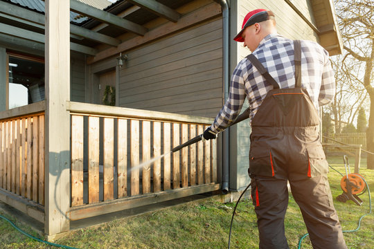Man cleaning terrace with a power washer - high water pressure cleaner on wooden terrace railing