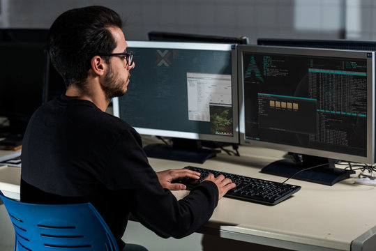 Young computer science student developing with his computer on a Linux System over double screen system