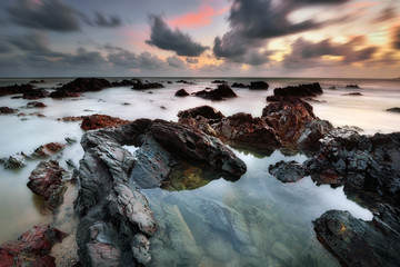 Wall Mural - Long exposure seascape over the rocky beach during sunrise in Terengganu, Malaysia. Nature background.
