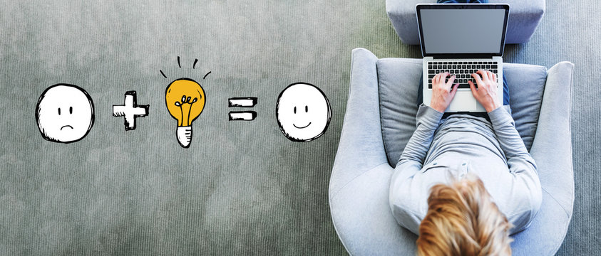 Good idea equals happy with man using a laptop in a modern gray chair
