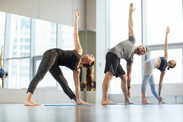 Group of young yoga students standing in row and doing trikonasana while stretching chests at class in modern studio