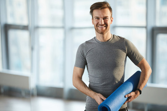Smiling handsome young male yoga coach with cool hairstyle and stubble holding yoga mat and looking at camera while standing in own studio