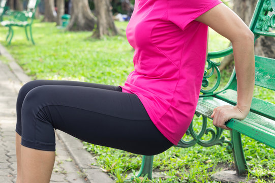 Woman doing triceps dips with bench.