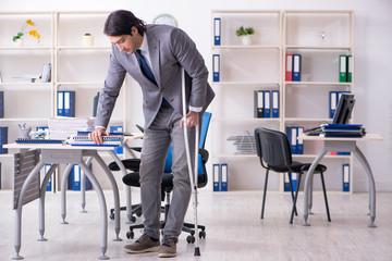 Fototapeta Leg injured male employee working in the office