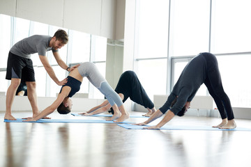 Content handsome young qualified yoga coach assisting students at class: he correcting downward facing dog pose of young woman