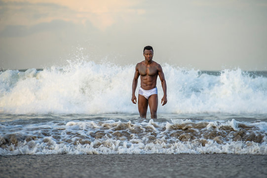 attractive and fit black African American man with sexy muscular body and sixpack abs posing cool on beach with big sea waves and foam around in beauty and health concept