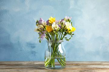 Obraz Bouquet of fresh freesia flowers in glass vase on table - fototapety do salonu
