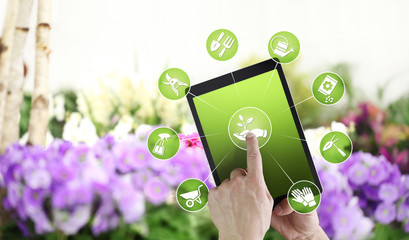 gardening equipment e-commerce concept, online shopping on digital tablet, hand pointing and touch screen with green tools icons, on spring flower plants background