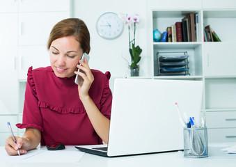Woman taking notes while talking