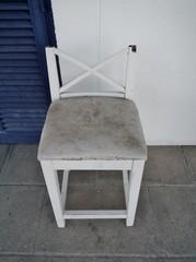 Defekter Stuhl vor Wand