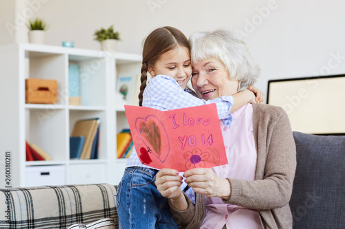 Portrait of cute little girl hugging grandma and giving her handmade I love you card on Valentines day, copy space
