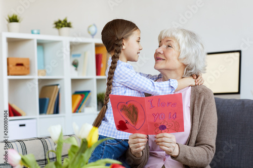Portrait of cute little girl hugging grandma and giving her handmade card on Birthday, copy space