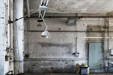 Lampe an einem Arbeitsplatz in einer stillgelegten verlassenen Werkstatt
