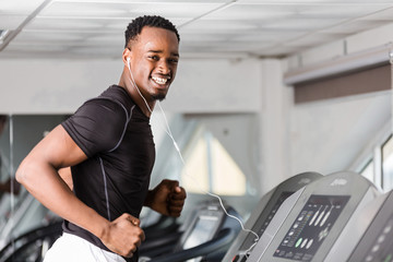 Black African American  young man doing cardio workout at the gym