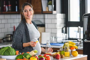 Beautiful smiling young pregnant woman preparing healthy food with lots of fruit and vegetables at home kitchen