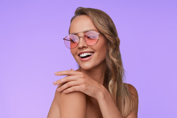 Portrait of beautiful young woman with perfect makeup wearing pink sunglasses. Smiling fashion model in aviator sunglasses posing on lilac background. Studio shot. Summer vacation.