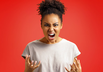 Annoyed girl gestures and shouts in anger. Photo of african american girl wears casual outfit on red background. Emotions and pleasant feelings concept.