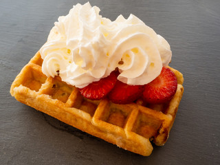 A Belgian waffle with cream over strawberry pieces on a slate plate