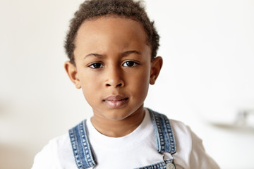Grumpy cute little boy of African appearance dressed in denim jumpsuit and white t-shirt acting naughty, doesn't want to go to bed, staring at camera, frowning his eyebrows, being in bad mood