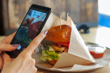 girl takes a picture of tasty burger set. social media concept.