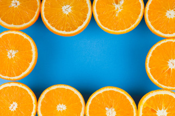 Cut halves of juicy orange on blue background. Orange fruit, citrus minimal concept. Creative...