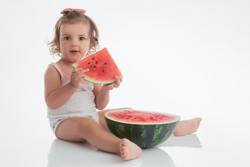 Baby girl eating watermelon slice isolated on white background