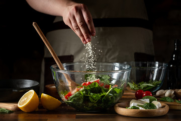 Cooking diet salad by chef hands adding salt on background with ingredients. Wall mural
