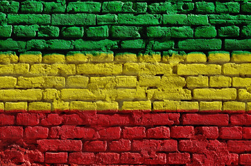Brick wall painted in green, yellow and red. Rastaman flag.
