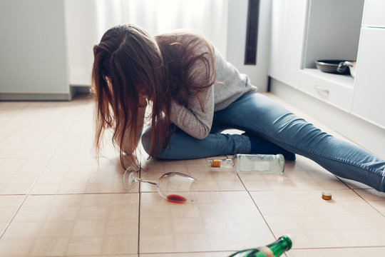 Female alcohol addiction. Young woman woke up on kitchen floor after party surrounded with wine bottles. Hangover