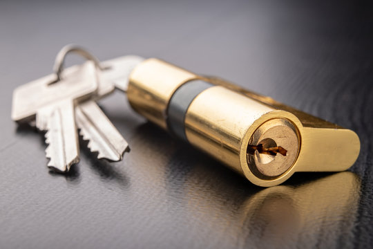 A new door lock on a dark background. A patent and keys to secure the front door.