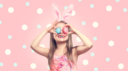 Funny Easter smiling little girl wearing bunny rabbit ears, holding colorful painted Easter eggs on her eyes. Baby girl laughing portrait over Polka Dots pink background