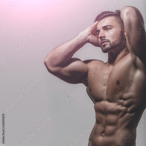 21917980288 Portrait of handsome guy with strong muscular body on blue background.  Fashionable trend in male's body and appearence. Handsome young man with  nude torso