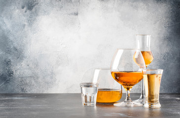 Set of hard strong alcoholic drinks and spirits in glasses in assortment: vodka, cognac, tequila, brandy and whiskey, grappa, liqueur, vermouth, tincture, rum. Gray bar counter