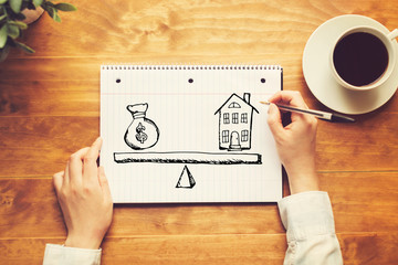 House and money on the scale with a person holding a pen on a wooden desk
