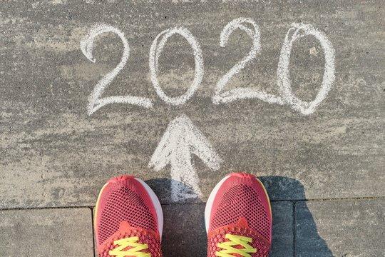 2020 arrow forward, written on gray sidewalk with woman legs in sneakers, top view